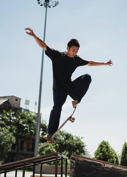 Sportive Asian man doing trick on skateboard
