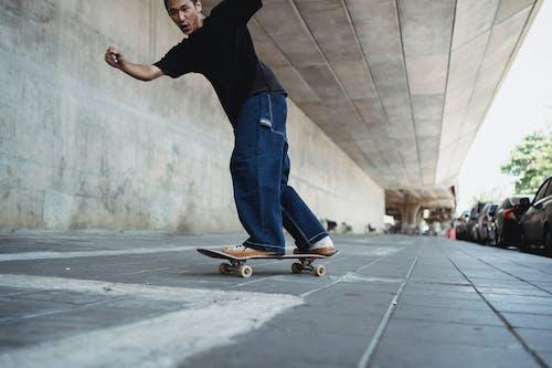 Cheerful Asian man riding on skateboard