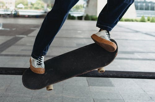Crop man jumping on skateboard