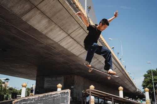 From below of sportive Asian male skateboarder jumping on railing with outstretched arms near bridge while performing trick in street