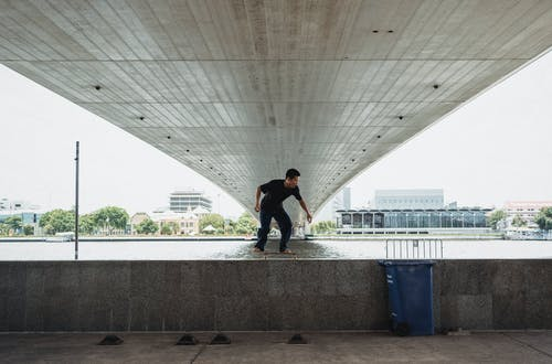Full body of unrecognizable male riding on skateboard on railing near sea under bridge during training on seaside in city