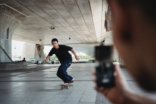 Full body of sportive man riding on skateboard under bridge and looking at camera of smartphone during training in street