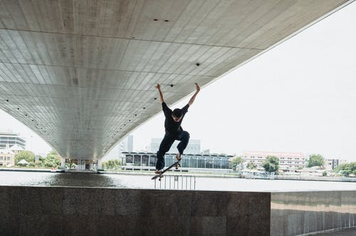 Millennial man doing trick with skateboard on waterfront