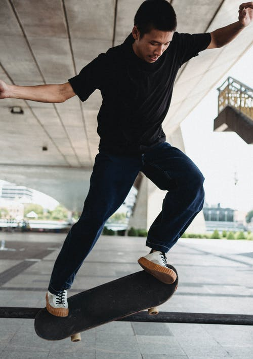Full body of sportive male with outstretched arms leaping on skateboard while doing stunt on pavement under bridge in city on street