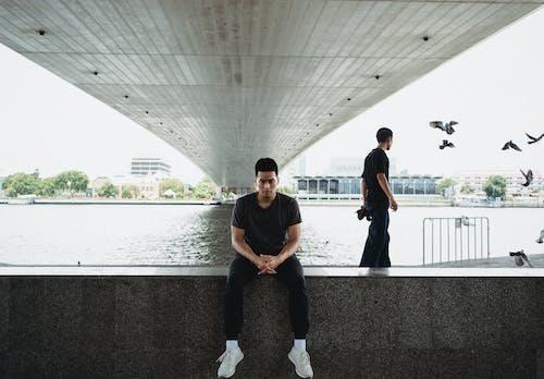 Asian man sitting on embankment under bridge