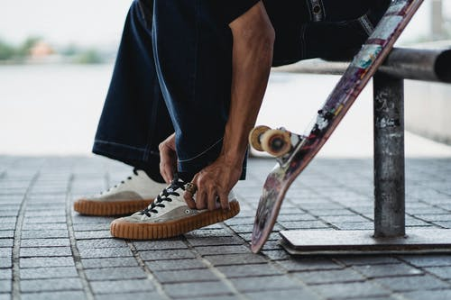 Side view of crop anonymous male wearing trendy sneakers and preparing for skateboarding on street