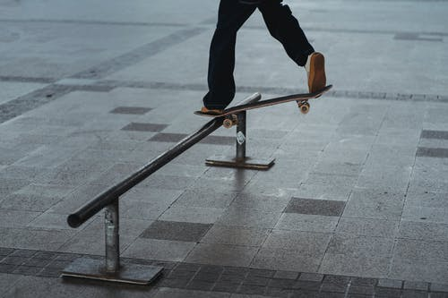 Homem Demonstrando Manobra Com Skate Sobre Corrimão De Metal
