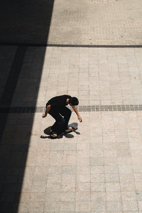 From above of young slim male moving on skateboard on concrete tile on sunny day