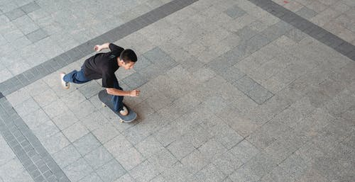 From above young male in casual outfit riding skateboard in park of modern city in summer