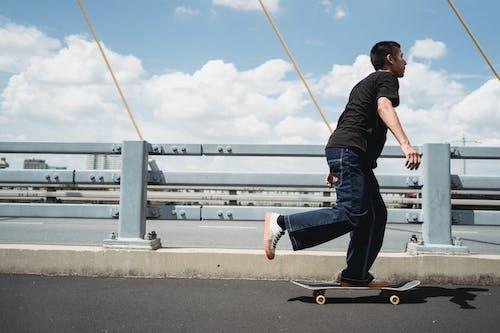 Active man riding skateboard on city bridge