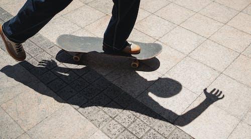 Crop skater on sidewalk in summer