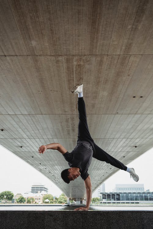 Full body of strong Asian man in sportswear performing handstand exercise during training on ground under bridge