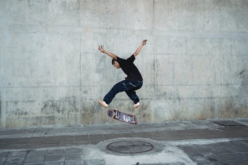 Young man jumping with skateboard above manhole near concrete wall
