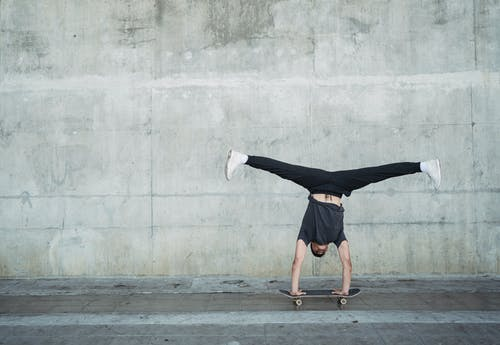 Anonymous guy in activewear doing handstand on skateboard while riding alone near concrete wall and pavement