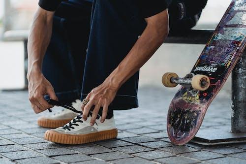 Snijd Jongeman Schoenveters Op Witte Sneakers In De Buurt Van Skateboard