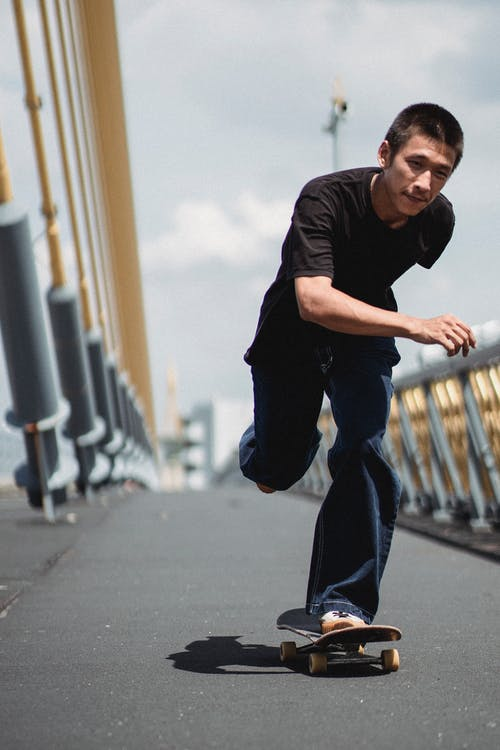 Happy young man riding skateboard on one leg along modern cable-stayed bridge