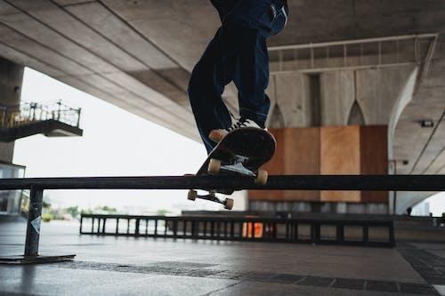 Unrecognizable skater doing grind trick on rail in skater training area