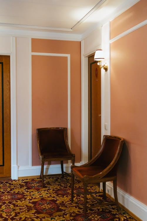 Black Wooden Armchair Beside Brown Wooden Door