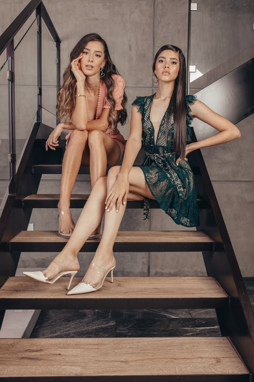 Full length attractive female models in designer trendy dresses sitting gracefully on staircase in modern cottage while looking at camera