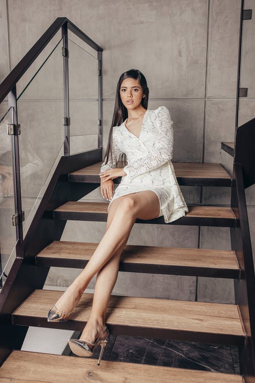 Full length gorgeous young female wearing white mini dress laying back with legs crossed on stairway in contemporary cottage and looking at camera