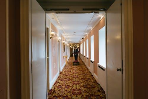 Person in Black Jacket Walking on Hallway