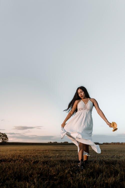 Woman in White Dress Walking on Field
