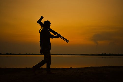 Full body side view silhouettes of anonymous male photographer with tripod admiring sunset while walking on coast of pond