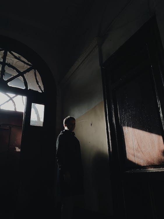 Man in Black Coat Standing Near Window