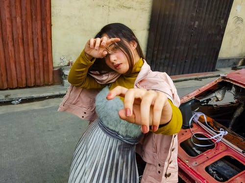 From above of young serious female in trendy outfit while standing near old damaged car