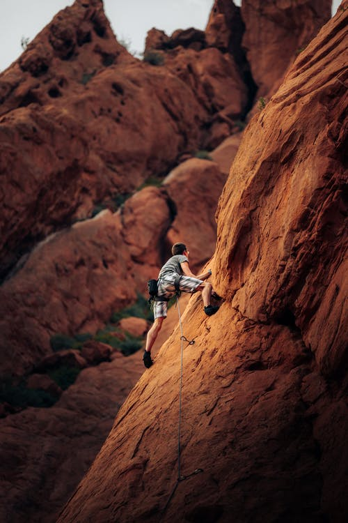 Man Rock Climbing on Mountain Side