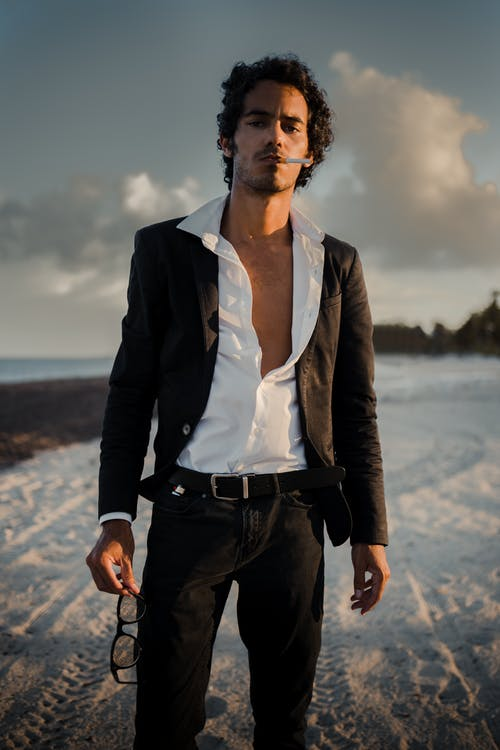 Man with Open Shirt and Smoking Standing on Beach