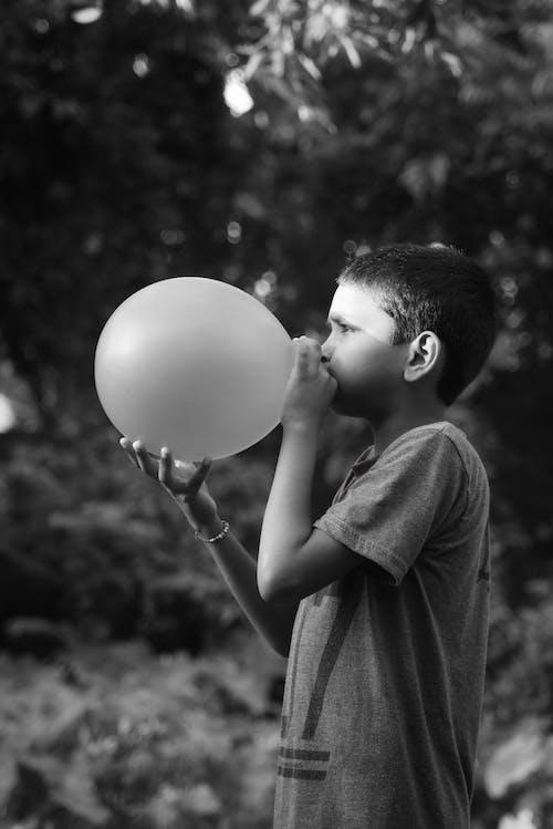 A Boy Blowing Up a Balloon