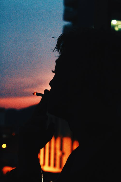 Calm person with burning cigarette smoking in dark evening