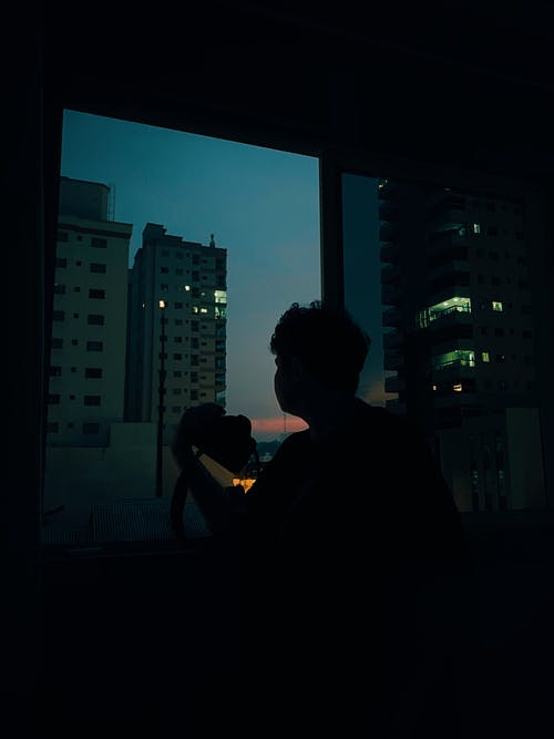Silhouette of anonymous man looking at window while resting in dark room in evening