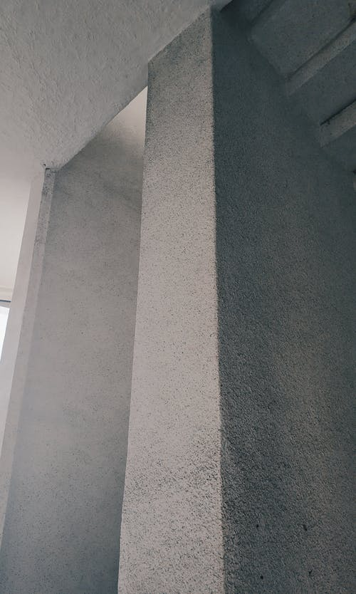 From below of edge of concrete textured gray wall in modern building with high ceiling