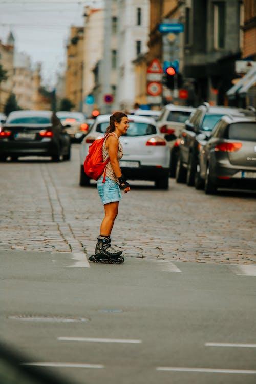 Woman in Orange Tank Top and Black Shorts Walking on Sidewalk
