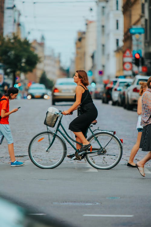Woman in Black Tank Top and White Shorts Riding on Bicycle