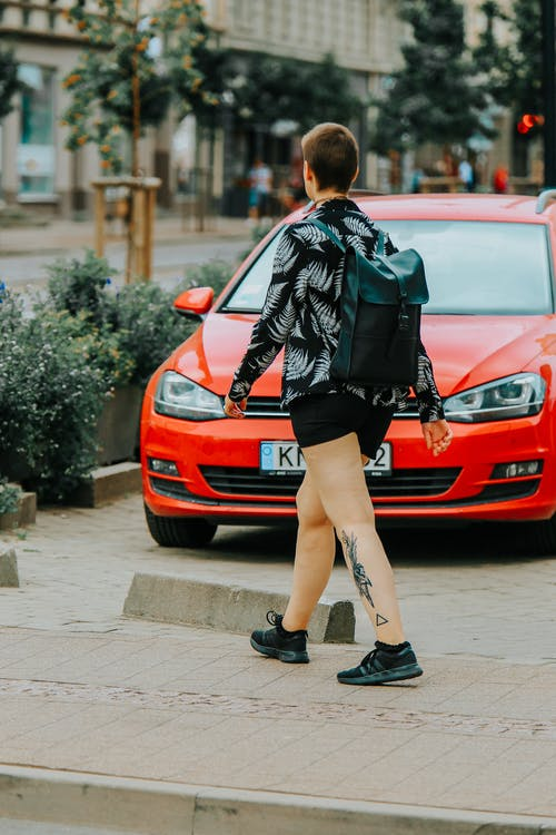 Woman in Black Leather Jacket and Black Shorts Standing Beside Red Car