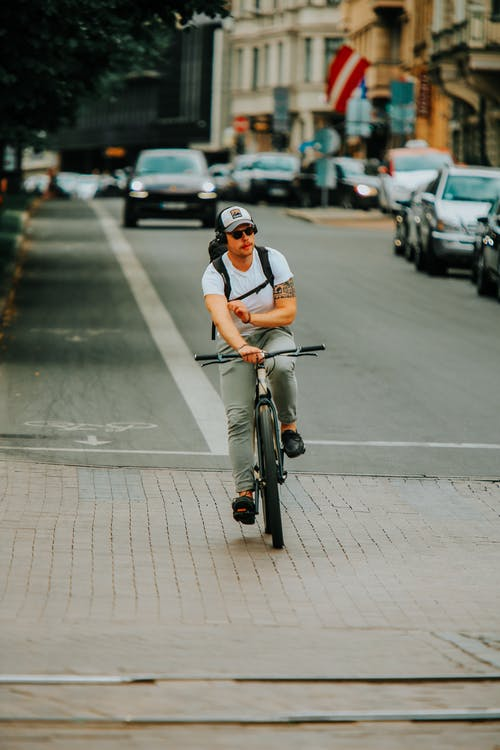 Woman in White T-shirt Riding Bicycle on Road