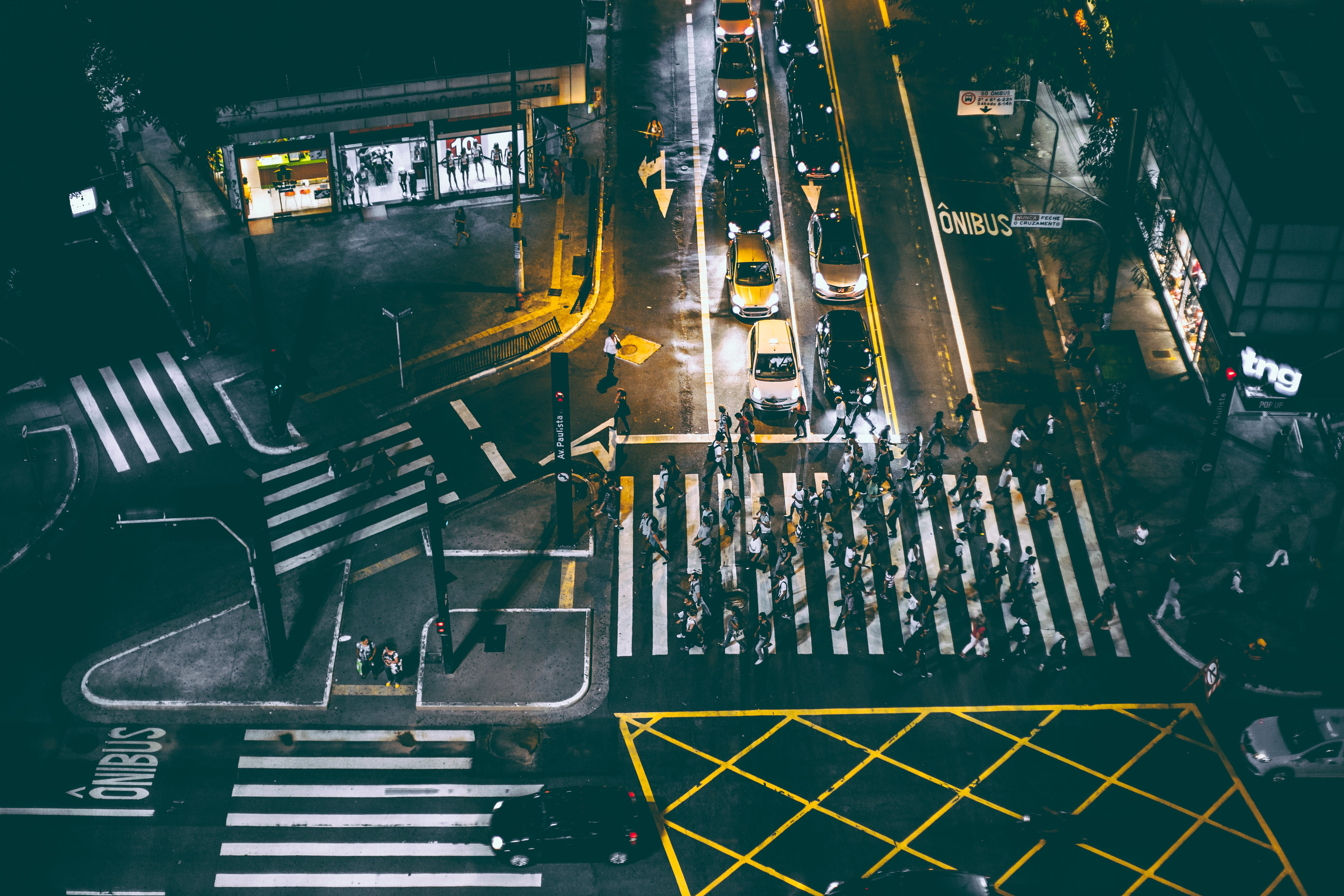 Aerial View of Bunch of People Walking on White Pedestrian Lane during Night