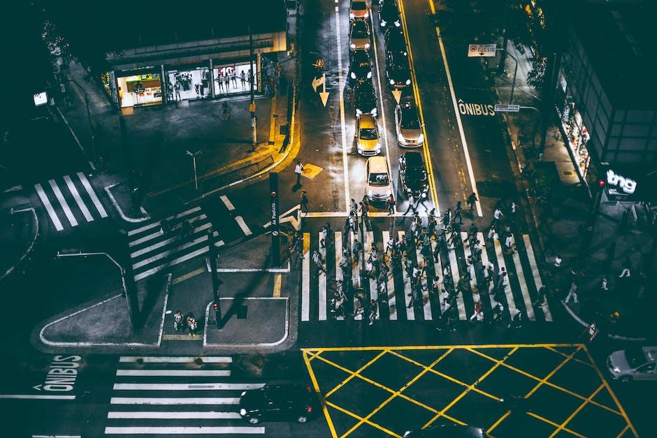 Aerial view of bunch of people walking on white pedestrian lane during night