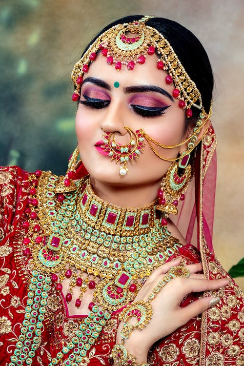 Beautiful Indian bride in traditional wedding red sari with golden embroidery heavy jewellery and bright make up