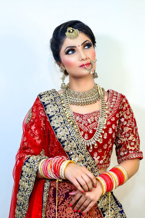Dreamy young Indian female wearing traditional red clothes with makeup and bracelets with necklace and earrings with piercing looking away on white background