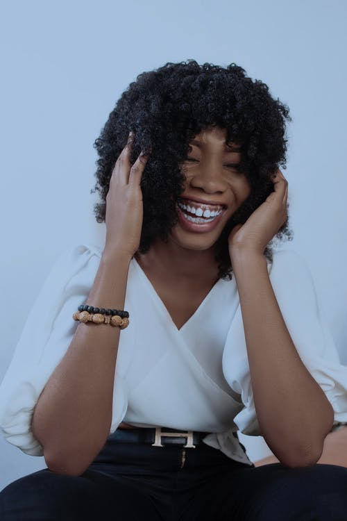 Black woman with curly hair laughing happily