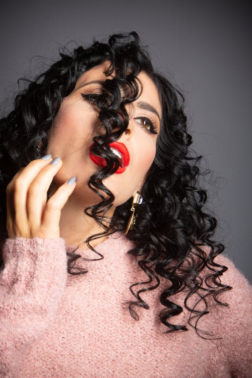 Sensual young with curly hair and mouth opened in studio