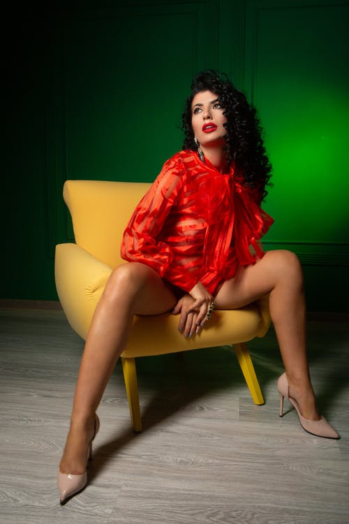 Full body of alluring female in blouse and high heels sitting on chair in studio and looking away