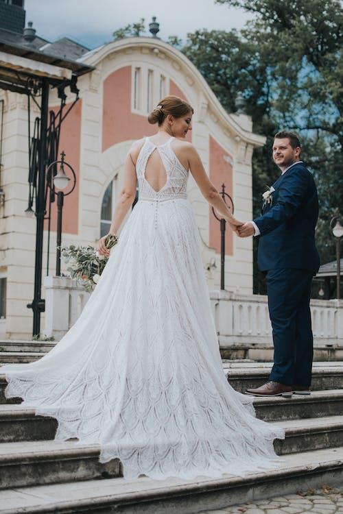 Elegant bride and groom holding hands during wedding celebration