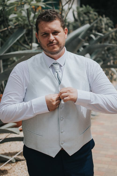 Confident bearded plus size groom wearing elegant formal clothes fastening buttons of elegant suit at wedding day