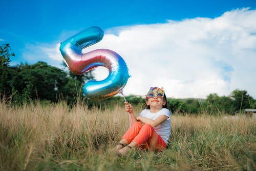 Girl Holding a Balloon while Sitting on Grass