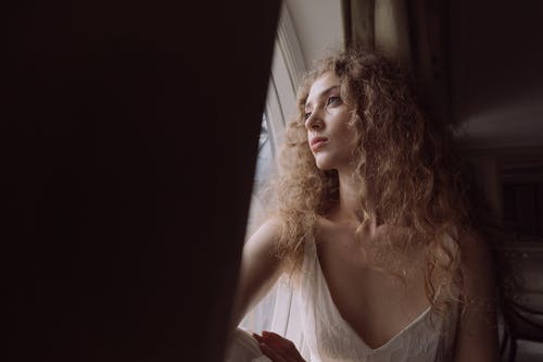 Woman in White Sleeveless Dress Looking Out a Window